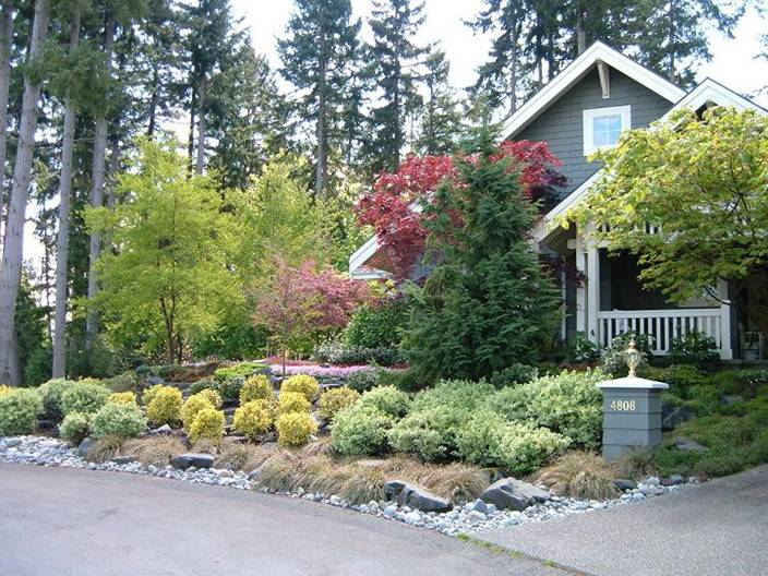 Curbside plant bed with river rock and shrubs